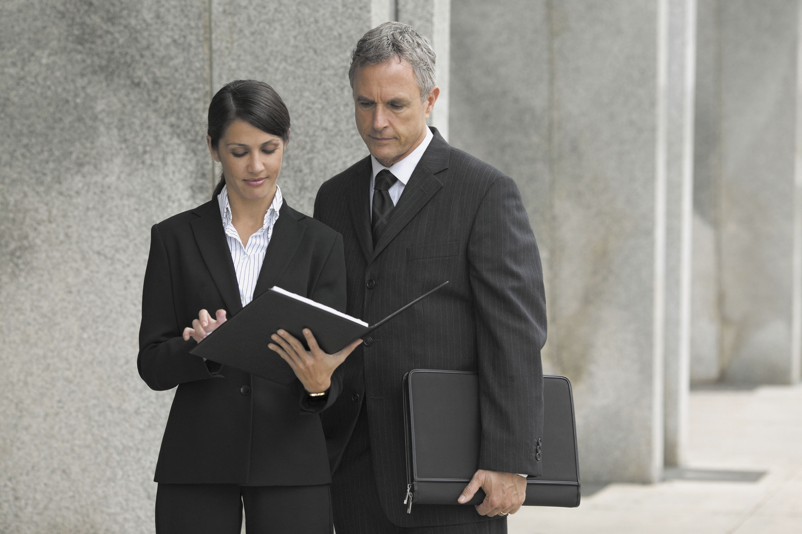 Businesswoman holding a file and businessman looking over her shoulder --- Image by © Royalty-Free/102363 - Corbis